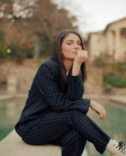 Portrait of Eve Hewson sitting by the pool in a suit