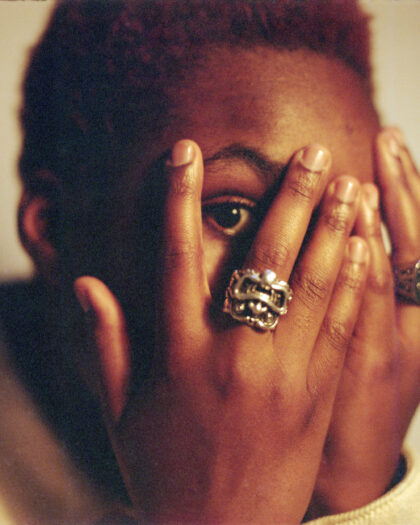 Portrait of musician Arlo parks with her hands on her face