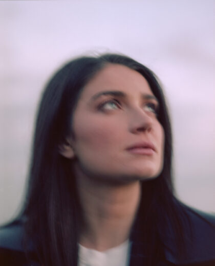 Portrait of Eve Hewson close up on her face, looking at the sunset on the beach