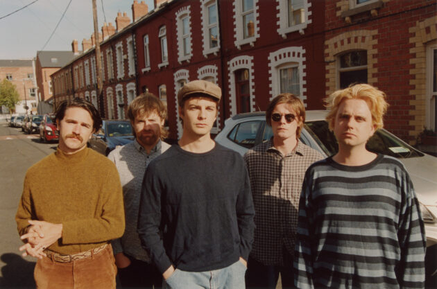 Press photo for Dublin band Fontaintes DC, group close to camera in ringsend
