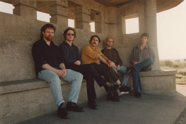 Press photo for Dublin band Fontaintes DC in a shelter by the sea in Bull Island