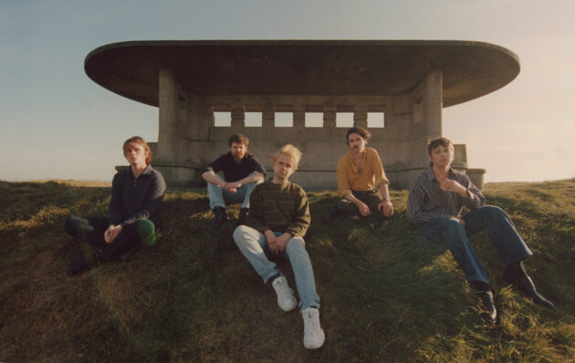 Press photo for Dublin band Fontaintes DC sitting on a hill on Bull Island