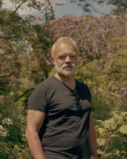 Portrait of Graham Norton at home standing in his garden