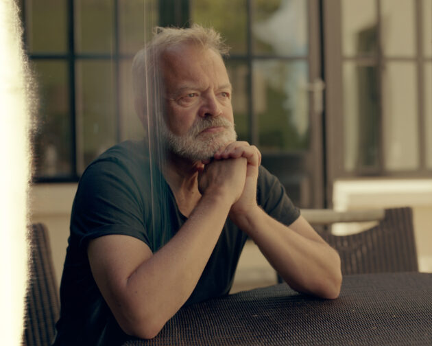 Portrait of Graham Norton at home sitting at a table outside, hands under his chin